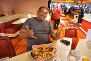 A man smiling as he eats food from Rainbow Club Casino's restaurant