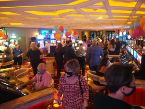 People walking around and playing on slot machines at Rainbow Club Casino