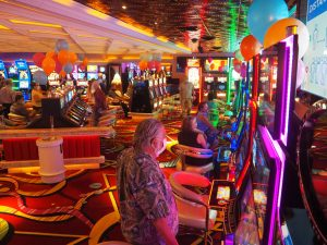 A row of Rainbow Club Casino guests playing on slot machines