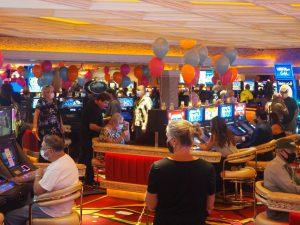 Rainbow Club Casino guests walking around and playing slot machine games