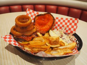 A close up of a burger with onion rings on it from Rainbow Club Casino's restaurant