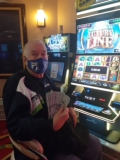 Bill holding up money he won from Rainbow Club Casino