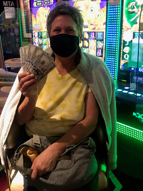 Lisa-G-holding-money-while-being-a-Rainbow-Club-Casino-Winner